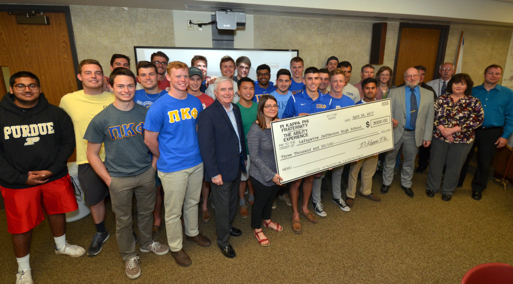 Fraternity members present check to Lafayette School Board